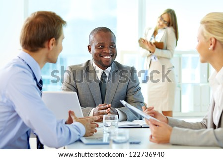 Portrait of confident boss smiling while interacting with his partners at meeting - stock photo