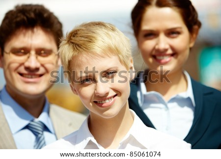 Portrait of confident business group looking at camera with pretty blonde at foreground
