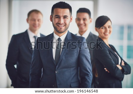 Portrait of confident business partners looking at camera with smiling leader in front - stock photo