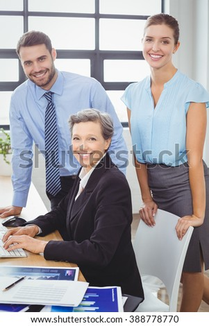 Portrait of confident business people at computer desk in office