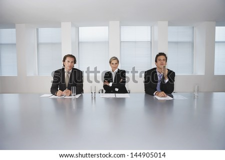 Portrait of confident business people sitting at conference table - stock photo