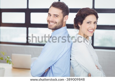 Portrait of confident business people standing back to back in office - stock photo