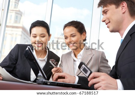 Portrait of confident business team gathered together at meeting and looking at the monitor of laptop with smiles - stock photo