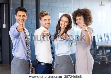 Portrait of confident business team smiling and pointing their fingers forward in office - stock photo
