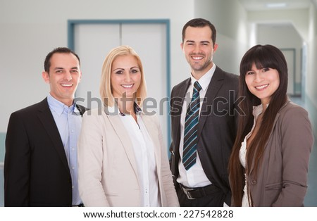 Portrait of confident business team smiling together in office - stock photo