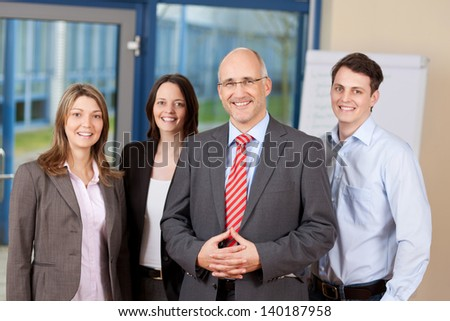 Portrait of confident business team standing together in office - stock photo