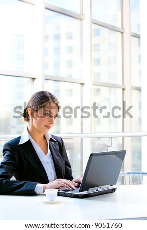 Portrait of confident business woman sitting at the table and typing a document on the laptop - stock photo