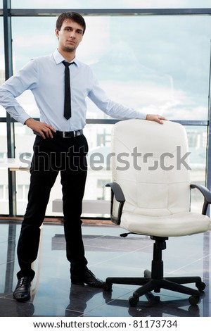 Portrait of confident businessman at his office standing near empty armchair and welcoming new employee. Recruitment concept - stock photo