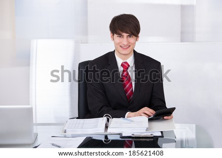 Portrait of confident businessman calculating finance using calculator at desk in office