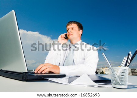 Portrait of confident businessman calling by mobile and typing on the laptop