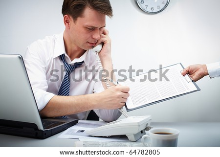 Portrait of confident businessman calling by phone while signing the contract held by his secretary