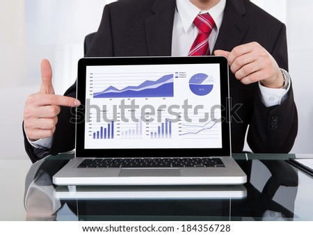 Portrait of confident businessman displaying laptop at desk in office - stock photo