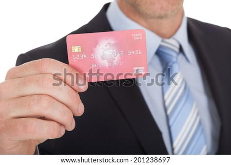 Portrait of confident businessman holding credit card over white background