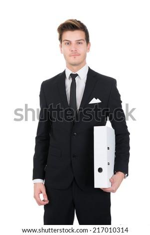 Portrait of confident businessman holding folder against white background - stock photo