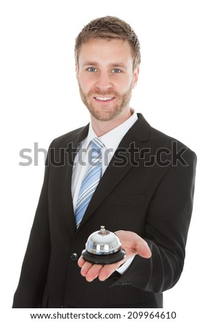 Portrait of confident businessman holding service bell over white background - stock photo