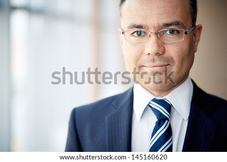 Portrait of confident businessman in eyeglasses looking at camera - stock photo
