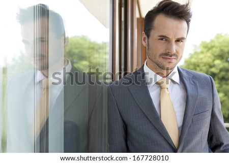 Portrait of confident businessman leaning on glass door - stock photo