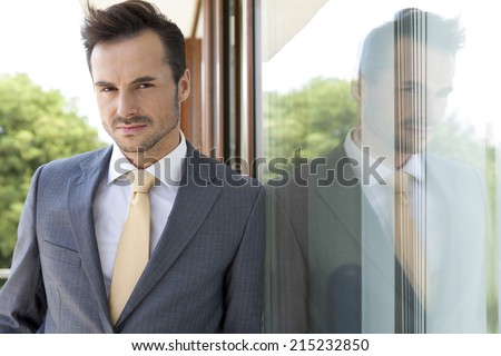 Portrait of confident businessman leaning on glass door - stock photo