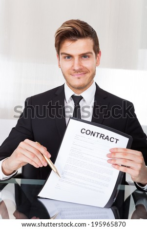 Portrait of confident businessman showing contract paper at desk in office