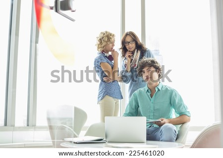 Portrait of confident businessman sitting at table with female colleagues conversing in background - stock photo