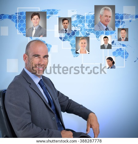 Portrait of confident businessman sitting on chair against background with hexagons and world map