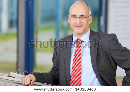 Portrait of confident businessman smiling while leaning on podium in office - stock photo