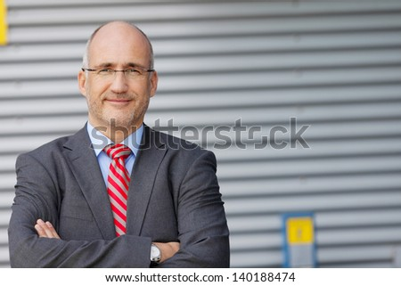 Portrait of confident businessman smiling with hands crossed against shutter - stock photo