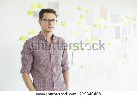 Portrait of confident businessman standing against whiteboard in creative office - stock photo