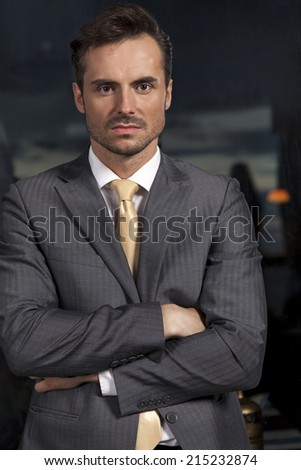 Portrait of confident businessman standing arms crossed in office - stock photo