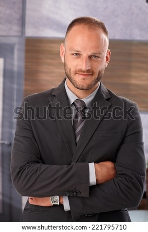 Portrait of confident businessman standing arms crossed, smiling, looking at camera. - stock photo