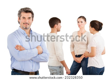 Portrait of confident businessman standing arms crossed with colleagues discussing over white background - stock photo