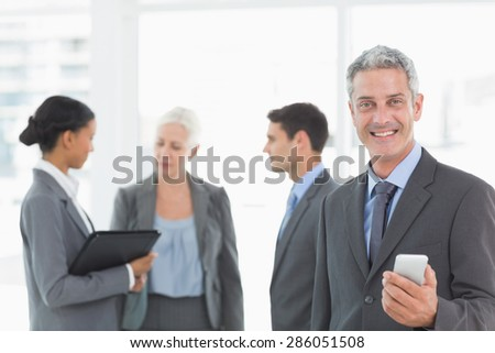 Portrait of confident businessman using a smartphone with colleagues behind in office - stock photo