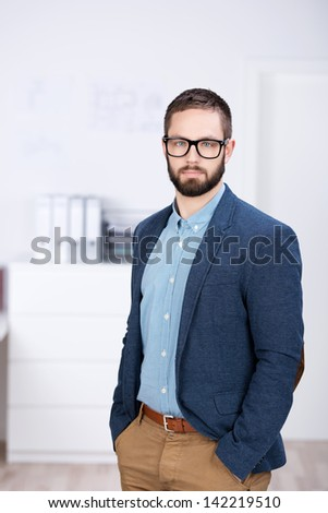 Portrait of confident businessman wearing glasses while standing with hands in pockets at office - stock photo