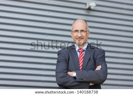 Portrait of confident businessman with arms crossed standing against wall - stock photo