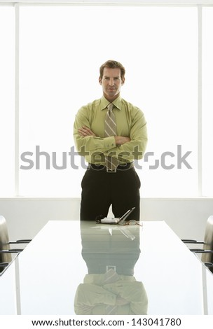 Portrait of confident businessman with arms crossed standing at conference table - stock photo