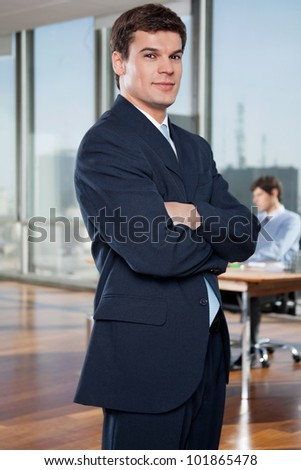 Portrait of confident businessman with arms crossed with colleague working in background - stock photo