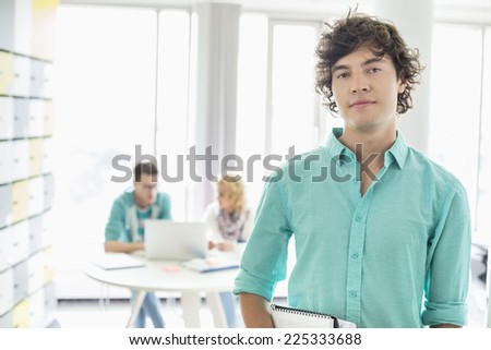 Portrait of confident businessman with colleagues working in background at creative office - stock photo