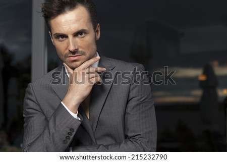 Portrait of confident businessman with hand on chin in office - stock photo