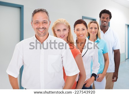 Portrait of confident businessman with multiethnic team standing in office