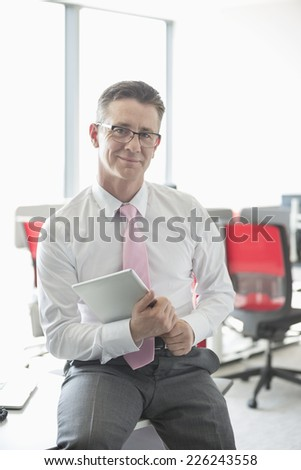 Portrait of confident businessman with tablet PC sitting on desk in office - stock photo