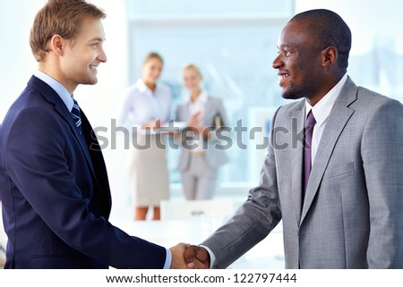 Portrait of confident businessmen handshaking and two females standing on background