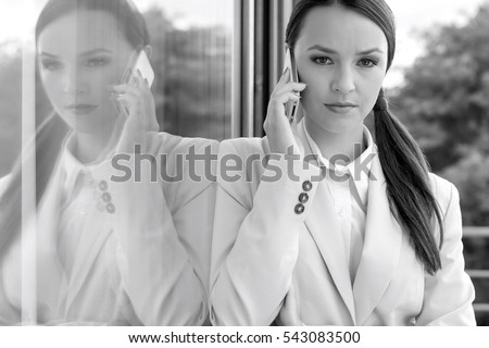 Portrait of confident businesswoman answering cell phone by glass door