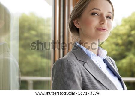 Portrait of confident businesswoman by glass door - stock photo