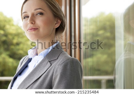 Portrait of confident businesswoman by glass door - stock photo