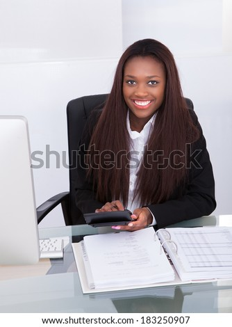 Portrait of confident businesswoman calculating tax at desk in office
