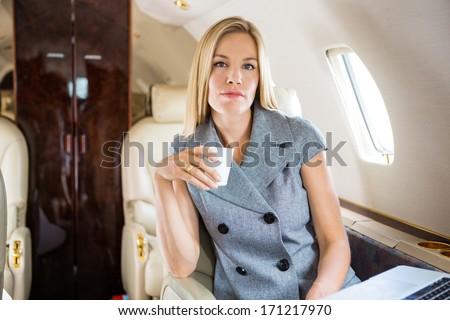Portrait of confident businesswoman having coffee in private jet - stock photo