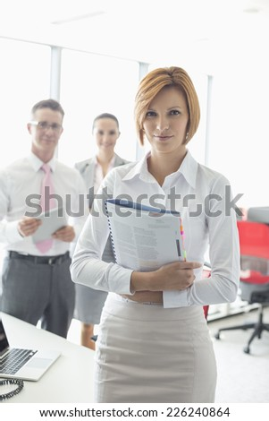 Portrait of confident businesswoman holding book with colleagues in background at office - stock photo