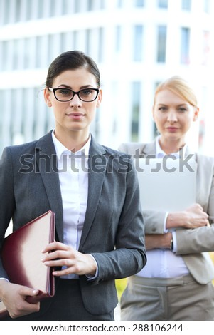 Portrait of confident businesswoman holding folder with colleague in background - stock photo