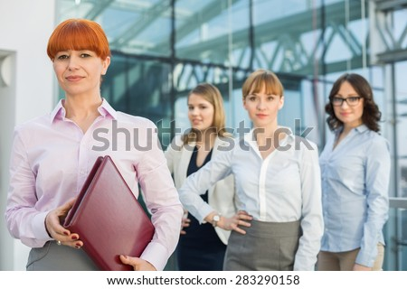 Portrait of confident businesswoman holding folder with female colleagues standing in background - stock photo