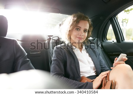 Portrait of confident businesswoman in back seat of car with her cell phone in hand looking at camera. - stock photo